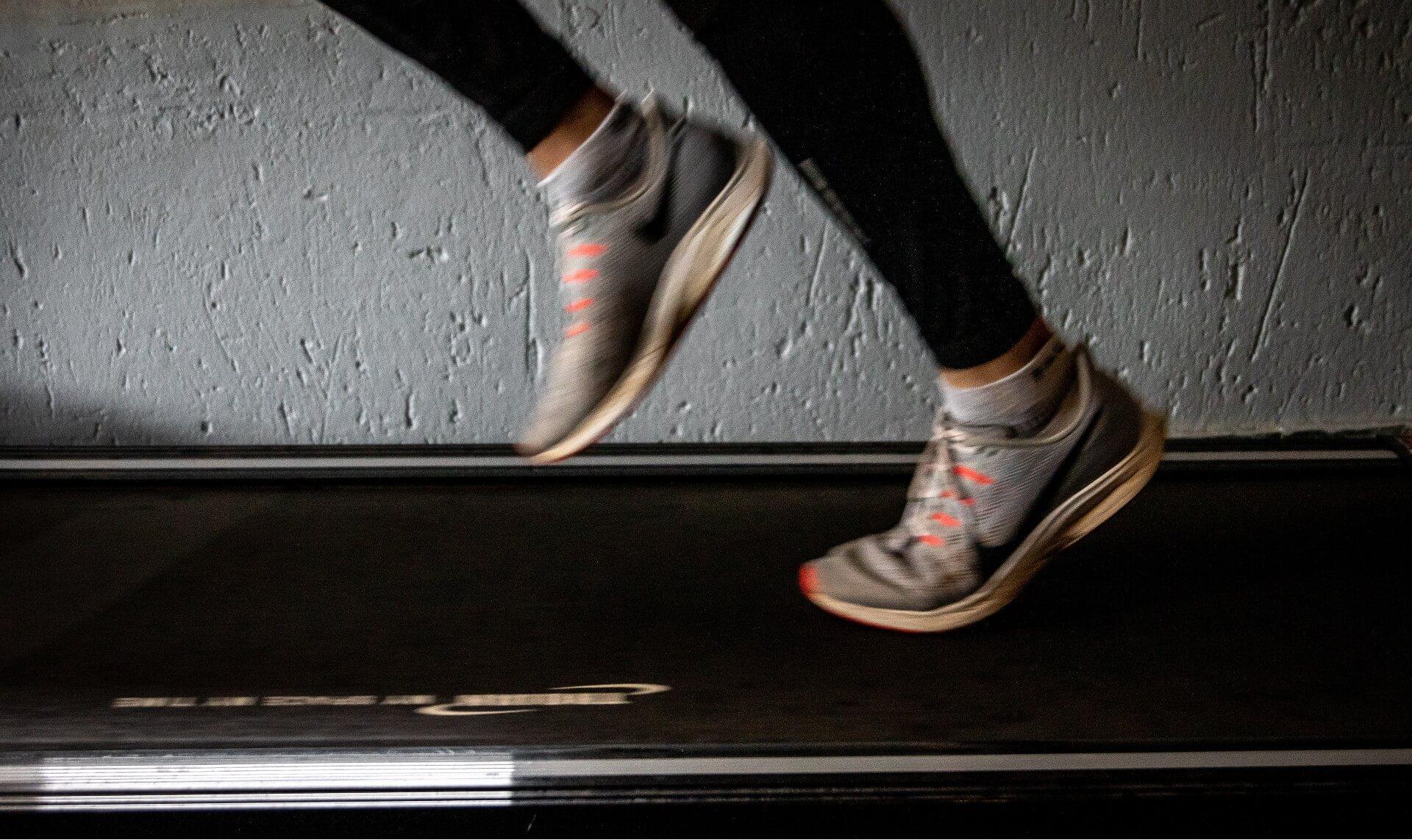 Closeup runner's feet on treadmill